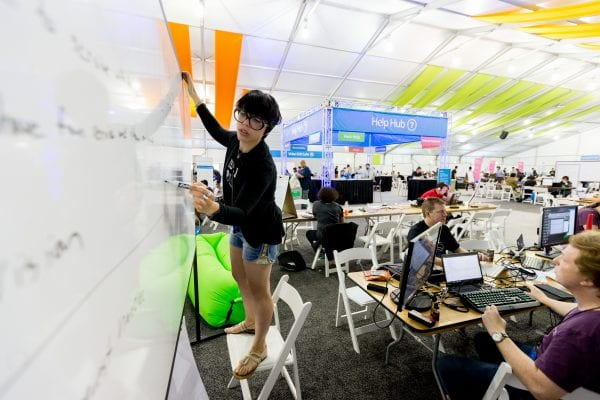 A past Hackathon participant writing on a whiteboard in a room full of people working on various projects at tables